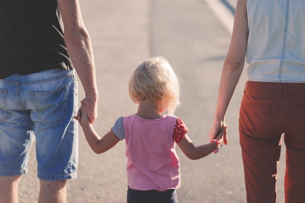 Child Holding Hands With Parents walking down the street