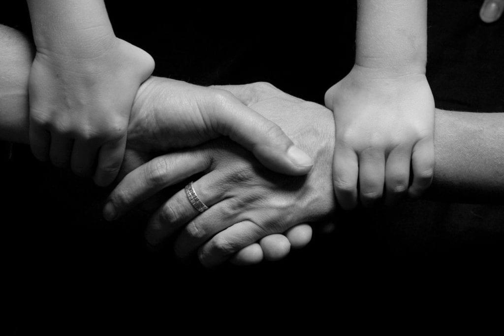 Child Holding Parents Hands Together