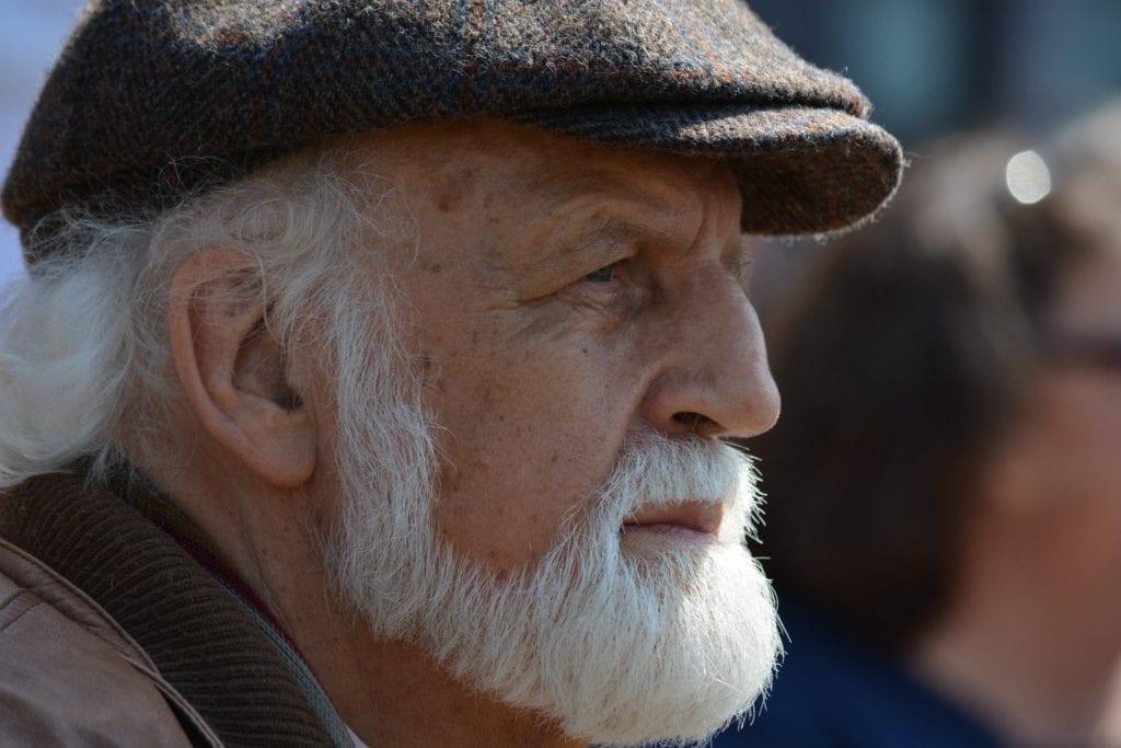 Old man with white beard staring